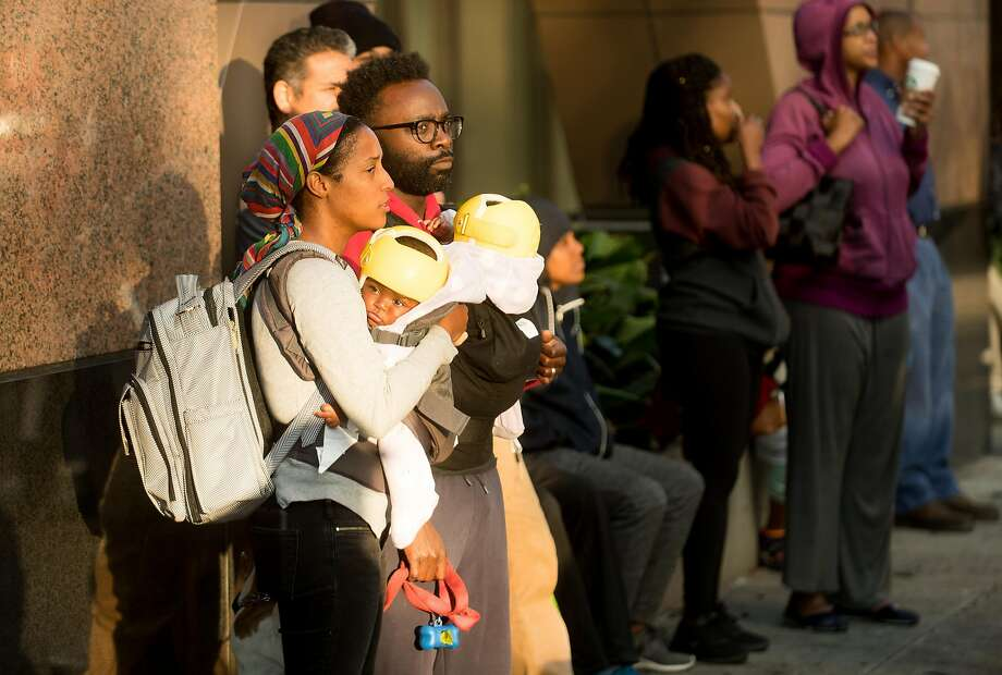 Leniece, left, and Delano Brissett hold their children while watching firefighters battle a building fire at Valdez and 23rd Streets in Oakland, Calif., on Friday, July 7, 2017. The couple lives across the street from the fire. Photo: Noah Berger, Special To The Chronicle