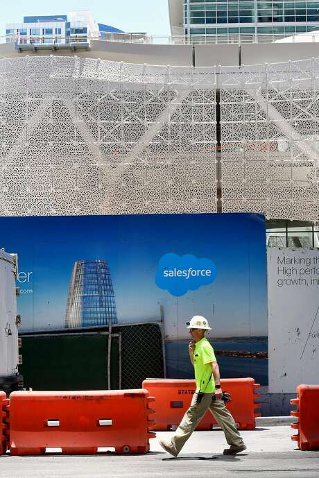 A construction worker walks past Salesforce Tower signs on the outside of the Transbay Terminal construction site in San Francisco, CA, on Friday July 7, 2017. Photo: Michael Short, Special To The Chronicle