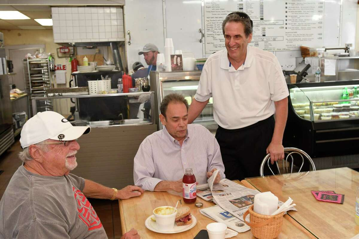 Fred Kaskowitz talks to longtime customers, Bob Zeisler, of Fairfield, and Randy Reich, of Trumbull, on a recent Friday at Woods End Deli in Bridgeport.