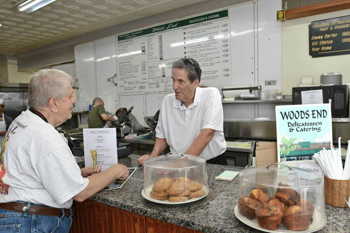 Fred Kaskowitz talks to longtime customer Joe Bender, of Fairfield, at the Woods End Deli in Bridgeport. Bender bought a bag full of the deli's homemade chocolate chip cookies.