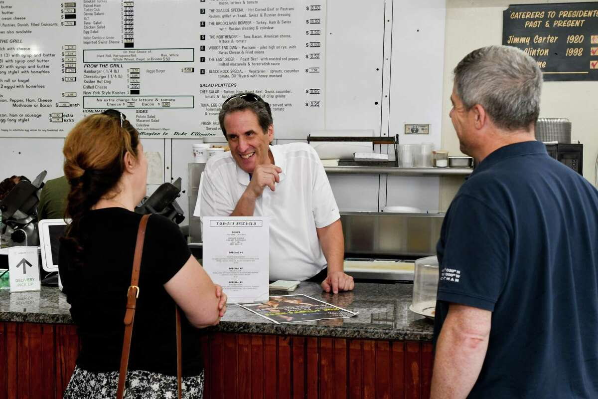 Fred Kaskowitz talks to customers Rosanne Johnson and her husband, Len Johnson, at Woods End Deli.