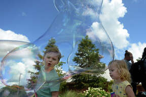 "during the Texas Energy Museum's ""Bubble Day"" event at the Rogers Park Community Center Friday. Several stations inside the center offered hands-on learning about the science of soap bubbles, while outdoors children played in the suds-filled pools, making and catching giant bubbles. Photo taken Friday, July, 7, 2017 Kim Brent/The Enterprise"