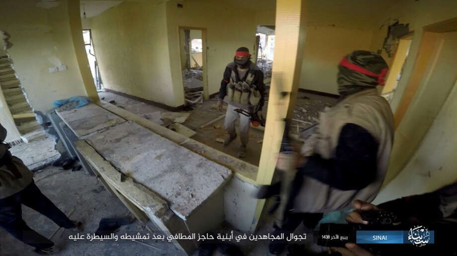 """FILE - This file photo posted on a file sharing website Wednesday, Jan. 11, 2017, by the Islamic State Group in Sinai, a militant organization, shows a deadly attack by militants on an Egyptian police checkpoint in el-Arish, north Sinai, Egypt. Egyptian officials say at least 10 security troops have been killed when a car bomb struck a military checkpoint followed by heavy gunfire in northeastern Sinai Peninsula. The officials say the Friday, July 7, 2017 attack started when a suicide car bomber rammed his vehicle into the checkpoint in southern Rafah village of el-Barth, followed by heavy shooting by dozens of masked militants on foot. Arabic reads, """"Walking around the building at the fire station after searching and taking control."""" (Islamic State Group in Sinai, via AP, File) Photo: Uncredited, HONS / Islamic State Group in Sinai"""