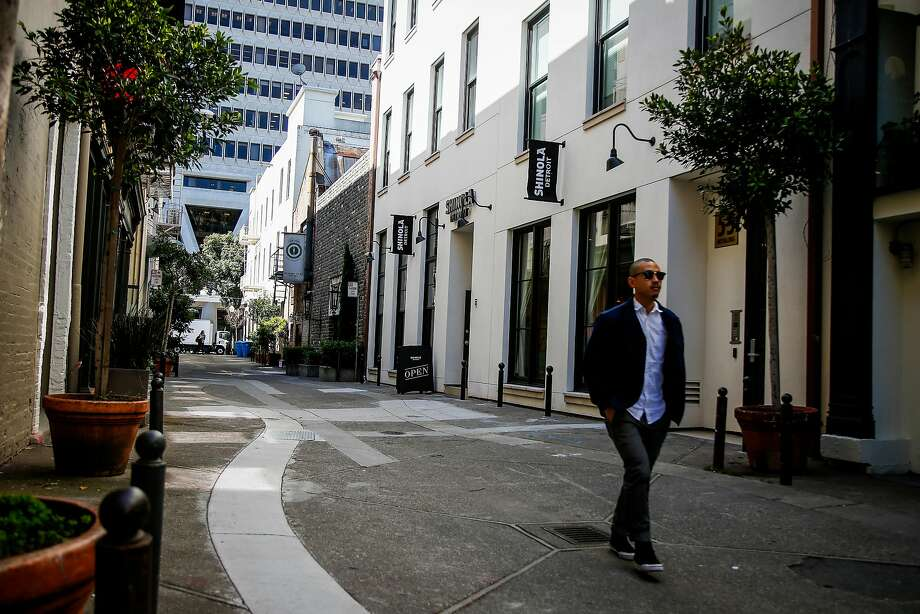 A shopper passes by Shinola and Allbirds, upscale retail stores, in the Jackson Square neighborhood of San Francisco in June 2017. Grosvenor America Inc. will construct condos at 288 Pacifica near upscale retail stores and historic buildings. Photo: Nicole Boliaux / The Chronicle 2017