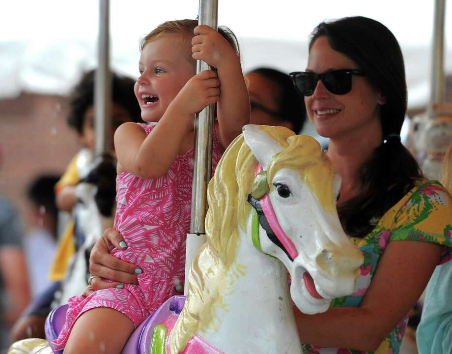 Aubrey Morgan, 3, of Old Greenwich takes a ride on the Merry-Go-Round with her mother Heather during the annual St. Roch's Feast last year. The Feast will return on Aug. 9. Photo: Matthew Brown / Hearst Connecticut Media / Stamford Advocate