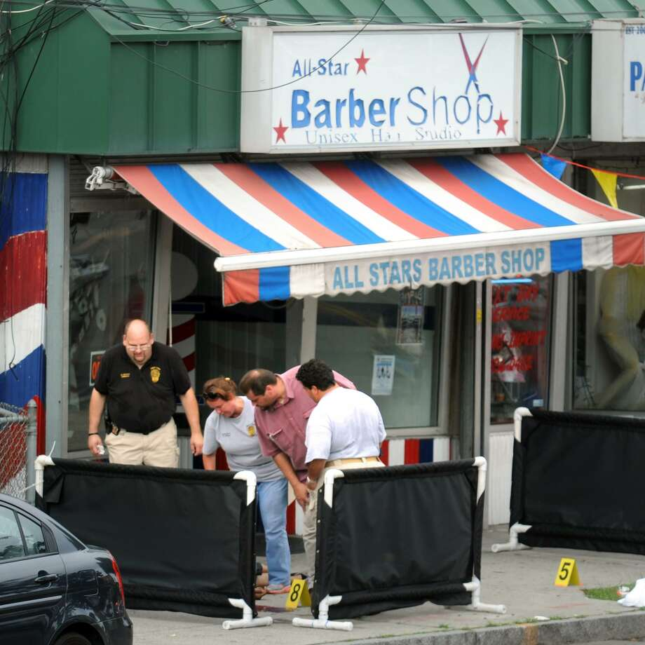 Bridgeport Police detectives look at the body of a man was shot and killed, hidden here behind portable partitions, in front of All-Star Barber Shop, on East Main Street, in Bridgeport, Conn. July 23rd, 2012. Photo: Ned Gerard / File Photo / Connecticut Post