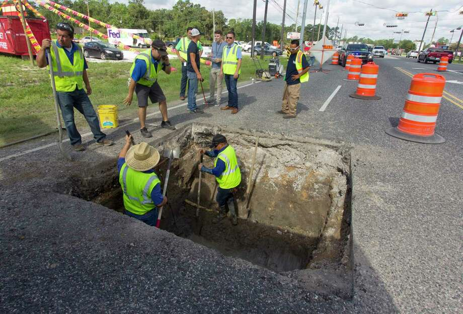 Workers with Montgomery County Precinct 3 work to get to a broken pipe that caused a sinkhole that shutdown one of the east bound lanes on Rayford Road near Wild Rose Drive, Friday, July 7, 2017, in Spring. Photo: Jason Fochtman, Staff Photographer / © 2017 Houston Chronicle