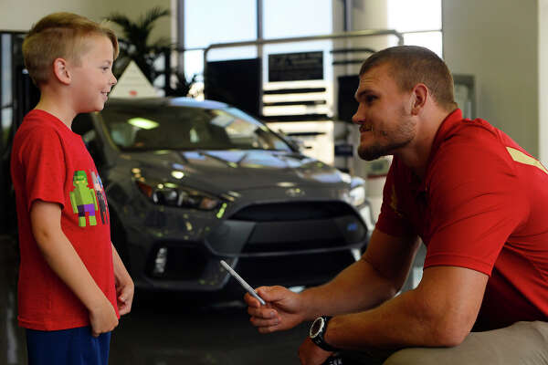 Nathan Oldbury, 8, talks with Vance McDonald, a Winnie native who plays tight end for the San Francisco 49ers, at Philpott Ford on Friday.  Photo taken Friday 7/7/17 Ryan Pelham/The Enterprise