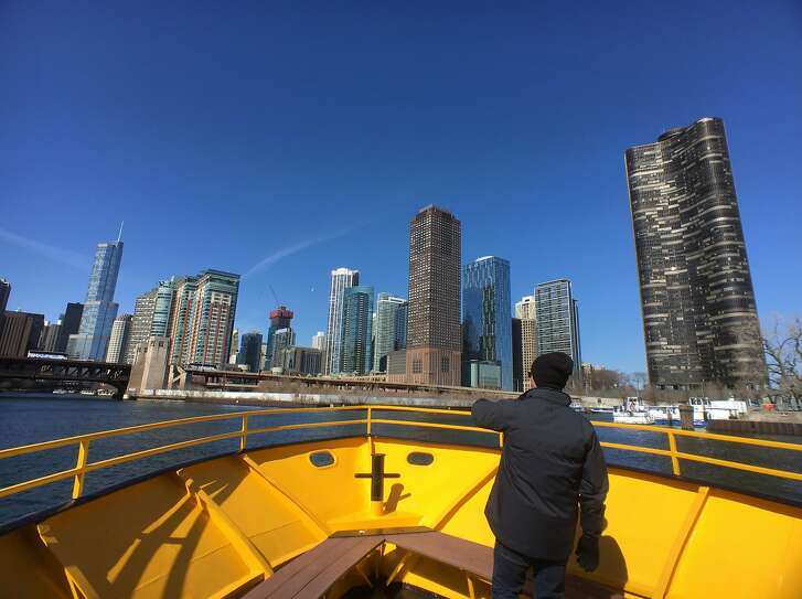 A worker at the bow of a Chicago Water Taxi vessel points down the South Fork of the Chicago River toward downtown.
