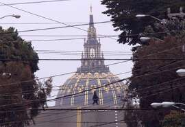 DOME/27MAY99/MN/BW--A woman crosses Fulton Street in San Francisco Thursday while the dome of City Hall looms in the background.  It was a gray day on the coast Thursday, but after the fog burned off visibility was descent.  City Hall is a good half mile from this pedestrian. By Brant Ward/Chronicle