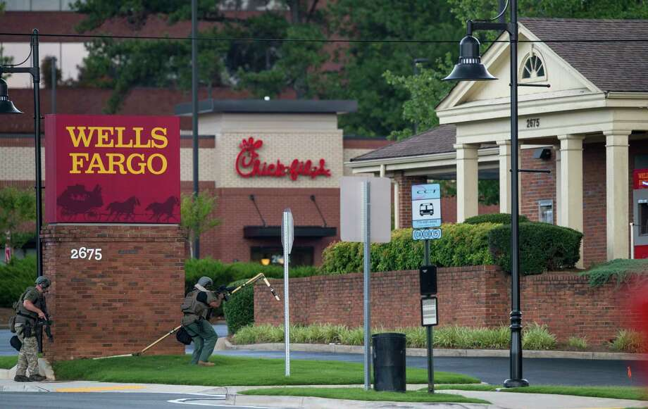 """Police officers move toward a Wells Fargo Bank, Friday, July 7, 2017 in Marietta, Ga. A man who claimed to have a bomb that could """"take out the room"""" barricaded himself inside a suburban Atlanta bank Friday, sparking an hours-long standoff that forced police to bust through a brick wall of the building and later ended with the suspect's death.(AP Photo/Mike Stewart) Photo: Mike Stewart, STF / Copyright 2017 The Associated Press. All rights reserved."""