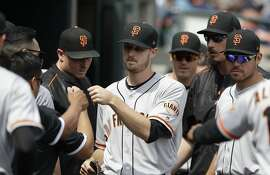 San Francisco Giants starting pitcher Chris Stratton is greeted by teammates after being relieved in the seventh inning of a baseball game against the Detroit Tigers, Thursday, July 6, 2017, in Detroit. (AP Photo/Carlos Osorio)