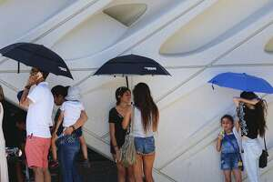 While waiting in line visitors at The Broad Museum, shade themselves from the afternoon heat in downtown Los Angeles on Friday, July 7, 2017. Southern California faces more blistering heat as firefighters around the state work to corral wildfires. The National Weather Service says high temperatures between 100 and 110 degrees will be common away from the coast Friday and Saturday while some coastal sections could see highs into the 90s. (AP Photo/Richard Vogel)