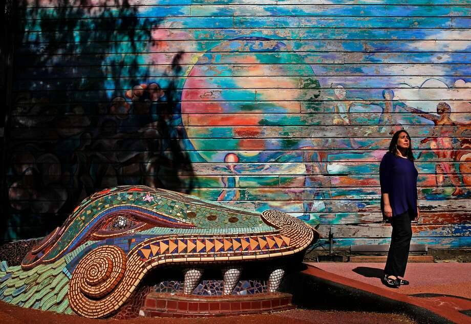"Author Cary Cordova, at the mini park at 24th and York streets, near the Michael Rios mural ""Children Dance Around the World,"" painted in 1982 and repainted in 1990, and Mark Roller's 1982 relief sculpture ""The Gifts of Quetzalcoatl."" Photo: Michael Macor, The Chronicle"