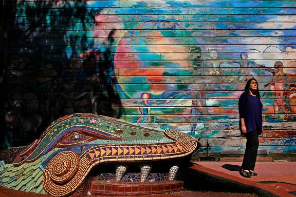 """Cory Cordova, at the 24th and York mini park in the Mission neighborhood, in San Francisco, Ca., on Thursday July 6, 2017. She is seen near the mural by�Michael Rios,�Children Dance Around the World, painted in 1982 and repainted in 1990�and the relief sculpture, """"The GIfts of Quetzal-Coatl"""" by Mark Roller, 1982 and one of the many murals that surround the park."""