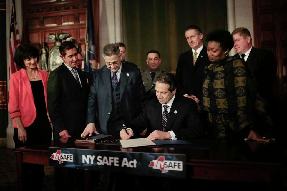 New York Gov. Andrew Cuomo signs the NY Safe Act into law in the Red Room of the New York State Capitol building in Albany N.Y., Jan. 15, 2013. The NY Safe Act, a sweeping package of gun control measures, which significantly expands a ban on assault weapons, makes New York the first state to change its laws in response to the mass shooting at a Connecticut elementary school. From second from left: New York State Senate Co-Leader Jeffrey Klein, Assembly Speaker Sheldon Silver, Cuomo and New York State Senate Democratic Leader Andrea Stewart-Cousins. (Nathaniel Brooks/The New York Times)