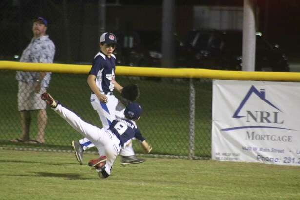 NASA-West right fielder Weston Ruemmele goes airborne in trying to haul in a fly ball that went a mile high in the air. Down 9-0, Weston's high-flying act was typical of the team's effort to the very end.