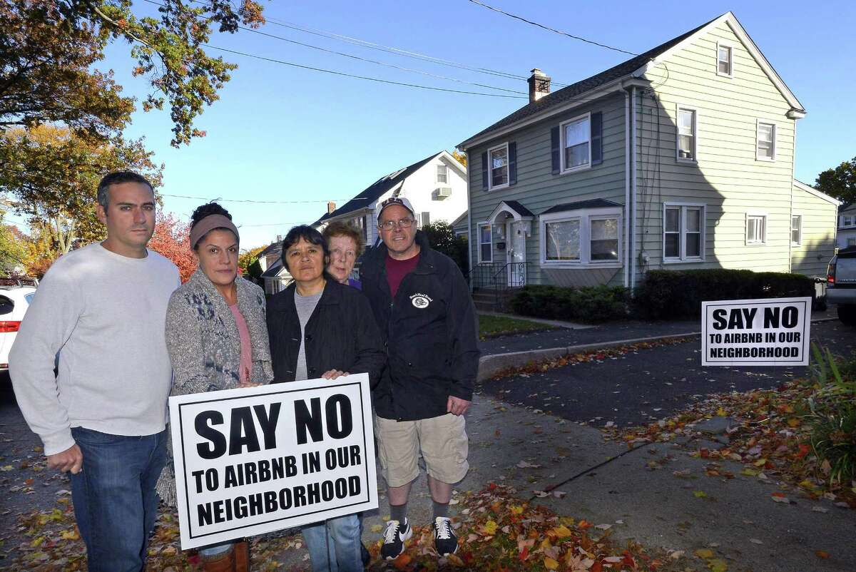 From left, Stephen Rich, Emily Ray, Gaby Pareja, Kathleen Connole and Anthony Rinaldi are photograph on Nov. 4, 2016, as they stand before the house at 20 Grandview Ave., at right, in Stamford's Hubbard Heights neighborhood, that was purchased in August and immediately turned into an Airbnb.