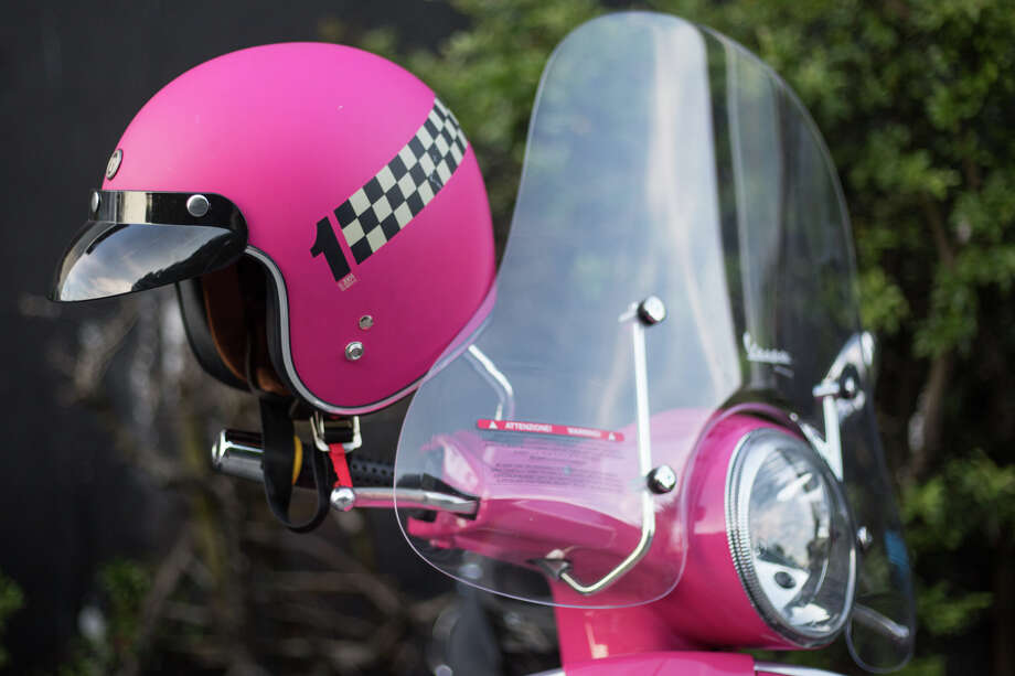 A bright pink Vespa and matching helmet sit outside China Harbor during the Amerivespa party on Friday, July 7, 2017. Photo: GRANT HINDSLEY, SEATTLEPI.COM / SEATTLEPI.COM