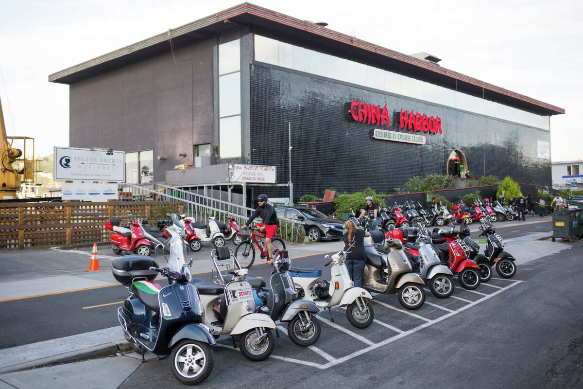 Scooters line up outside China Harbor during the Amerivespa party on Friday, July 7, 2017.