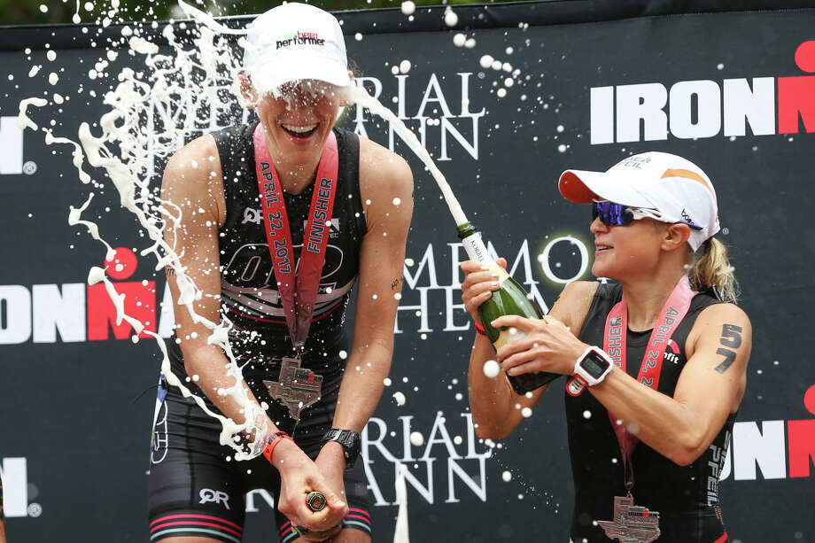 Michaela Herlbauer, of Austria, opens a bottle of champagne in the face of Jodie Robertson, of New York, during the Memorial Hermann IRONMAN North American Championship Texas on Saturday, April 22, 2017, in The Woodlands. Photo: Michael Minasi, Staff Photographer / © 2017 Houston Chronicle