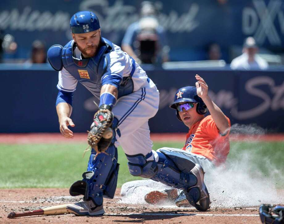 Houston Astros' Norichika Aoki, right, scores on a double by teammate George Springer as Toronto Blue Jays catcher Russell Martin handles the throw to home plate in the third inning of their baseball game in Toronto on Saturday, July 8, 2017. (Fred Thornhill/The Canadian Press via AP) Photo: Fred Thornhill, SUB / The Canadian Press