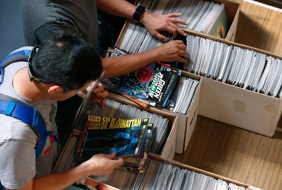 Comic book enthusiasts search thousands of titles at the sale at the Friends of the SF Public Library donation center. Photo: Paul Chinn, The Chronicle