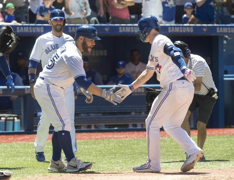 Toronto Blue Jays' Russell Martin, left, congratulates teammate Josh Donaldson after he hit a three-run home run against the Houston Astros in the fifth inning of their baseball game in Toronto on Saturday, July 8, 2017. (Fred Thornhill/The Canadian Press via AP) Photo: Fred Thornhill/Associated Press