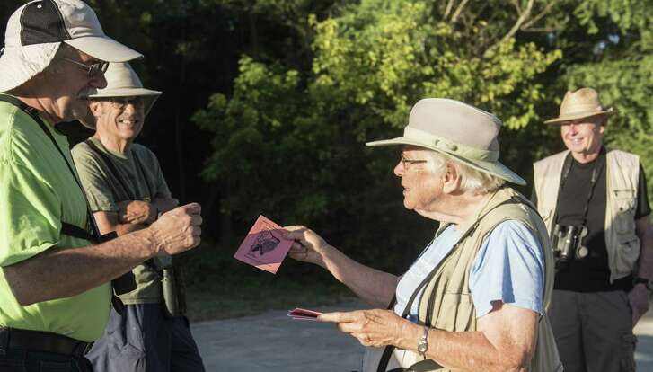 San Antonio Audubon Society's tour guide Georgina Schwartz hands a bird identifying note book to Ozzie Reguera during an early morning beginner's bird walk  at Judson Nature Trails in Alamo Heights.   Carlos Javier Sanchez / For The Express News