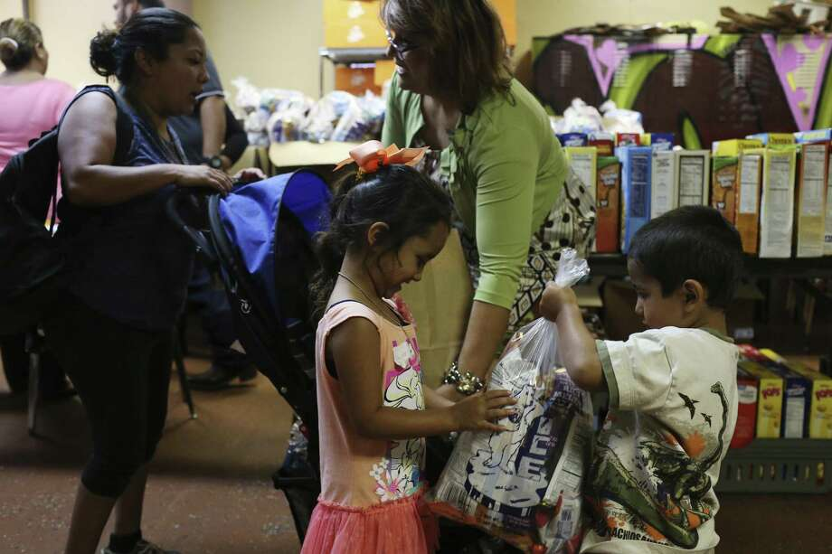 Harley Torres, 3, right, keeps his food bag away from his sister Haley Torres, 4, at Last Chance Ministries in the city's Westside, Sunday, June 18, 2017. The San Antonio Food Bank has partnered with school districts, nonprofits, and churches to ensure that children who depend on meals at school do not go hungry during the summer months. Pamela Espurvoa-Allen from Eagles Flight Advocacy & Outreach and volunteers hand out food packages to children through the 1+1+1 Initiative One Child-One Lunch Bag-One Week summer program. Photo: JERRY LARA / San Antonio Express-News / © 2017 San Antonio Express-News