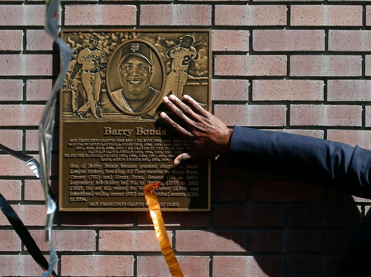As streamers fall from the sky, Barry Bonds reaches out to touch a plaque unveiled during a ceremony to enshrine the retired slugger on the Giants' Wall of Fame outside of AT&T Park on King Street in San Francisco, Calif. on Saturday, July 8, 2017.