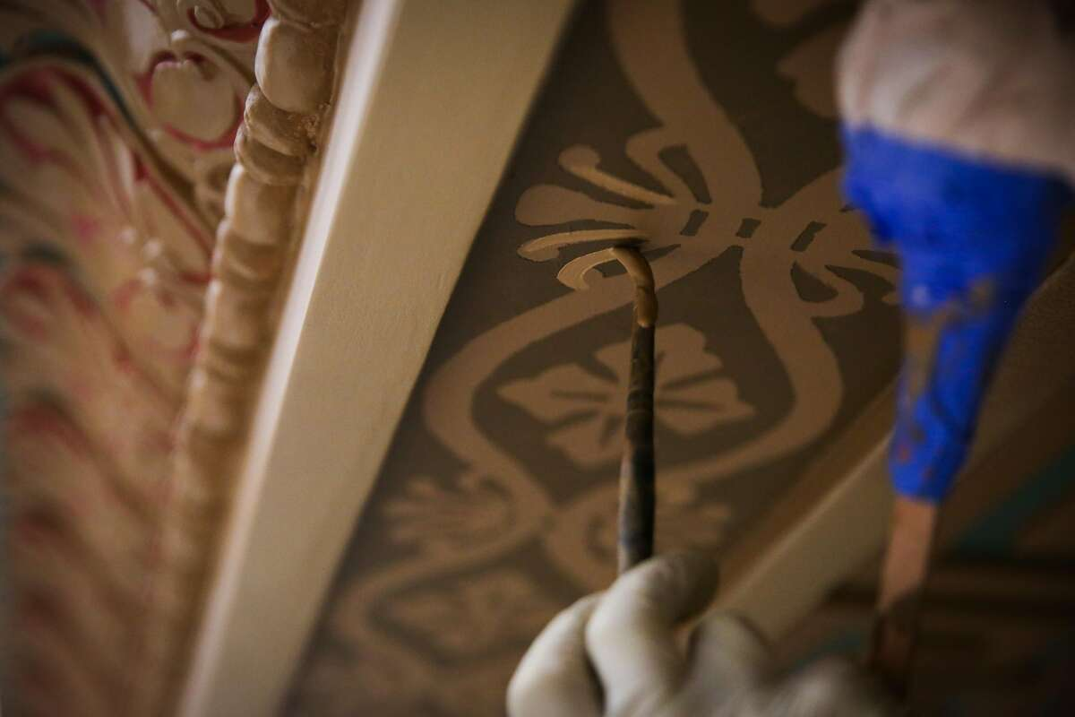 Beate Bruhl paints details on the ceiling of the Mining Exchange building.