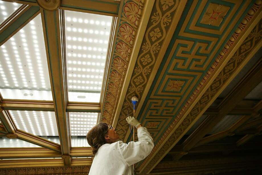 Conservationist Beate Bruhl paints the historic 45-foot high ceiling of the Mining Exchange building in San Francisco. Photo: Gabrielle Lurie, The Chronicle
