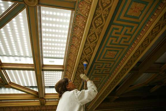 Conservationist Beate Bruhl paints the historic 45-foot high ceiling of the Mining Exchange building in San Francisco, California, on Monday, June 19, 2017.