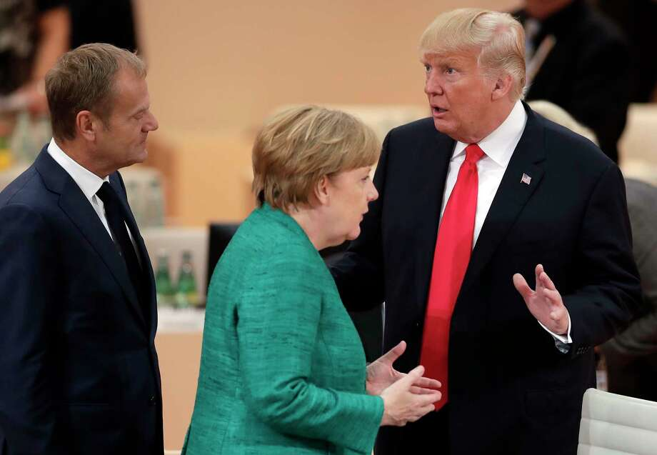 U.S. President Donald Trump, right, gestures as he talks to German Chancellor Angela Merkel, center, and European Council President Donald Tusk, left, during a working session at the G-20 summit in Hamburg, northern Germany, Saturday, July 8, 2017. The leaders of the group of 20 meet July 7 and 8. (AP Photo/Michael Sohn) ORG XMIT: SOB103 Photo: Michael Sohn / Copyright 2017 The Associated Press. All rights reserved.