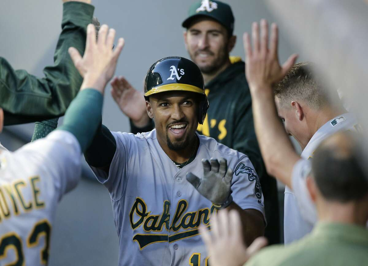 Oakland Athletics' Marcus Semien is congratulated in the dugout after hitting a solo home run off Seattle Mariners' Andrew Moore during the fifth inning of a baseball game, Saturday, July 8, 2017, in Seattle.