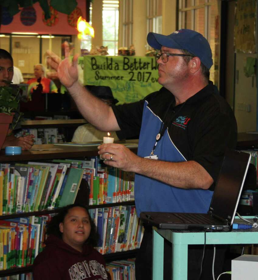 Billy Chmielewski of Space Center Houston demonstrates how heat works in creating fuel for rockets by lighting a piece of flash paper in front of children at Austin Memorial Library for their Summer Reading program on July 5. Photo: Jacob McAdams