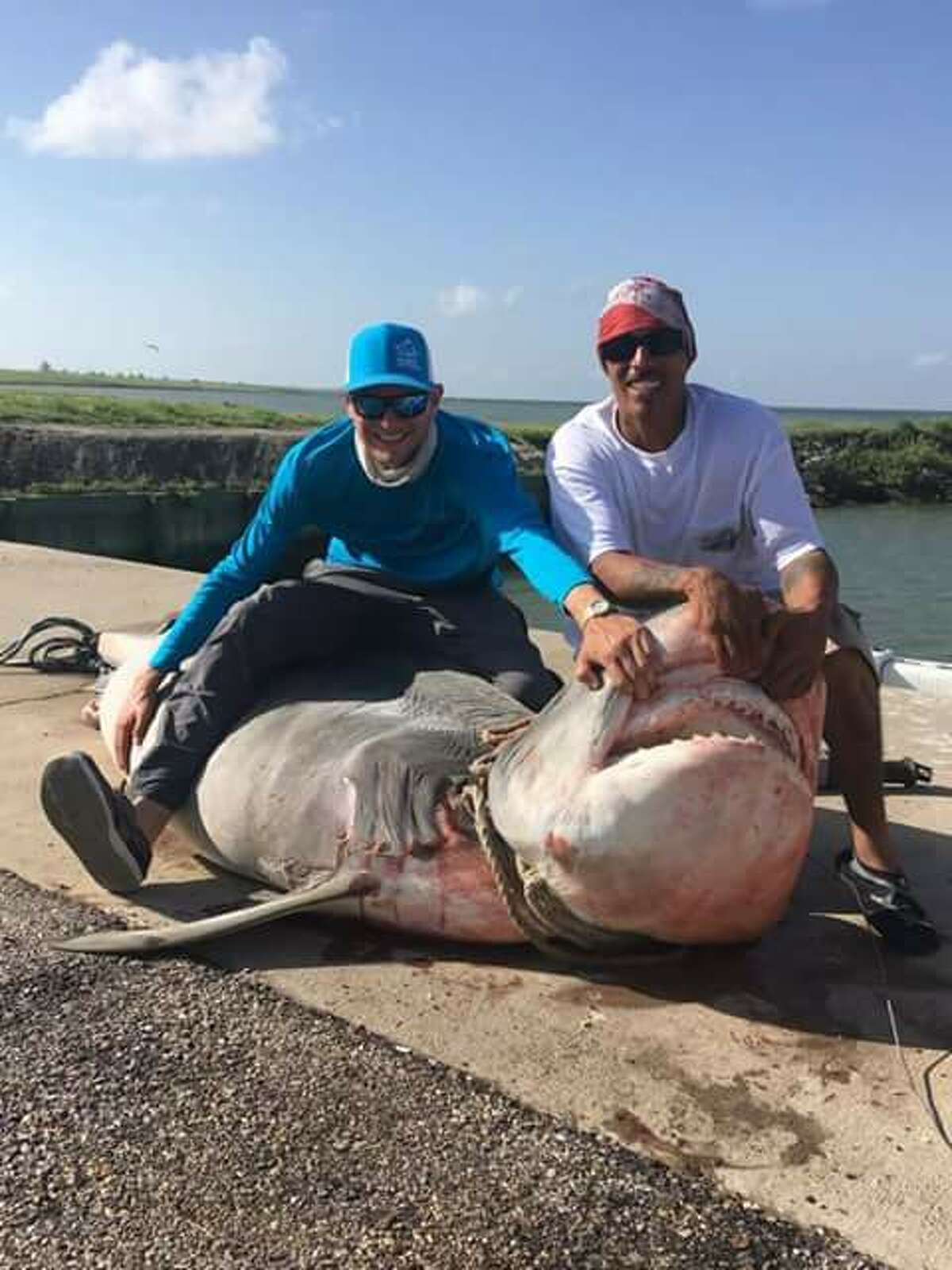 On Sunday, July 2, a massive 964-pound Tiger Shark was reeled in off the shores of Texas City by Sergio Roque (right). The huge catch is 85 percent of the Texas state record.
