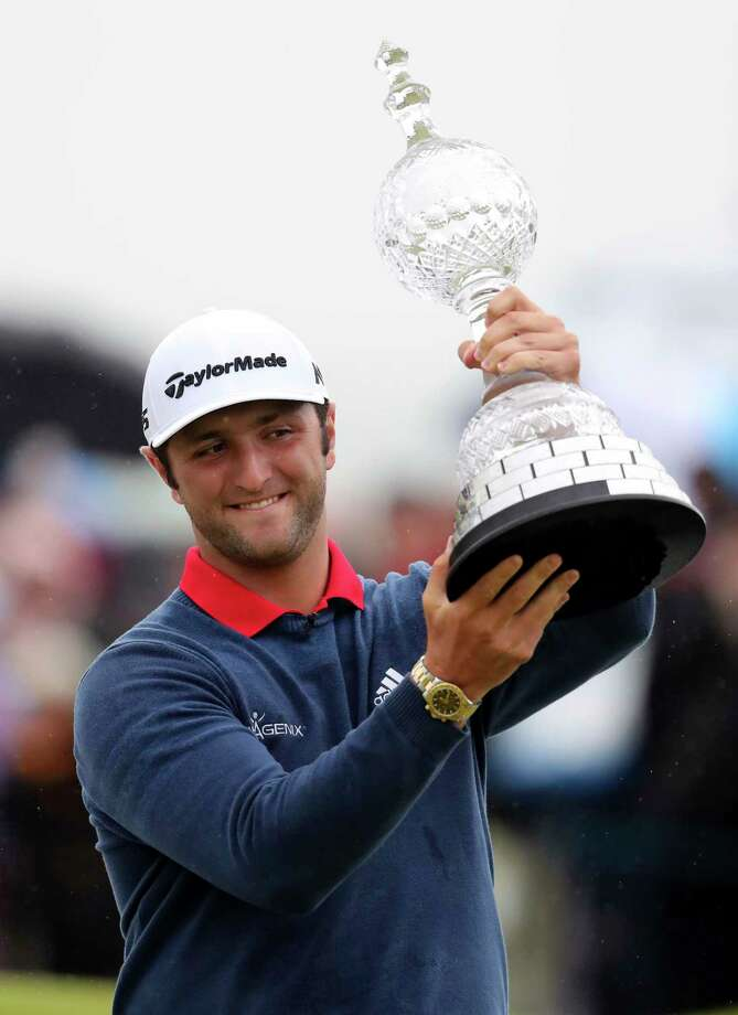 Spain's Jon Rahm lifts the trophy aloft after winning the Irish Open golf tournament at Portstewart Golf Club, Northern Ireland, Sunday July 9, 2017.  Rahm, one of the hottest young players in world golf, holed out from 150 yards for an eagle on No. 4 and strung together four straight birdies from No. 7 to turn what was promising to be a tight final day into a procession to win the tournament Sunday.  (Niall Carson/PA via AP) Photo: Niall Carson, SUB / PA Wire