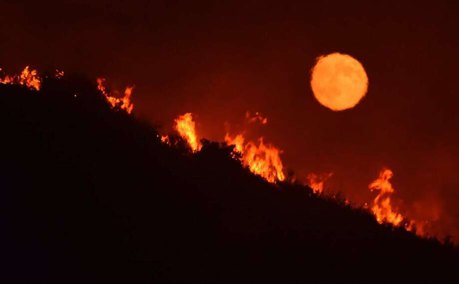 The moon rises over flames on a hilltop near Highway 166 east of Santa Maria (Santa Barbara County) Saturday. Photo: Mike Eliason, Associated Press