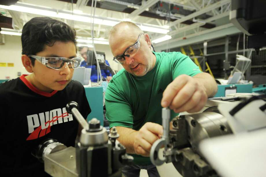 Precision maufacturing teacher Steve Orloski, right, shows Bayron Espinosa, 12, of Ansonia, how to measure thickness with a caliper as he uses an engine lathe in the Young Manufacturers Academy summer program at Emmett O'Brien Technical School in Ansonia, Conn. on Thursday, July 6, 2017. Photo: Brian A. Pounds / Hearst Connecticut Media / Connecticut Post