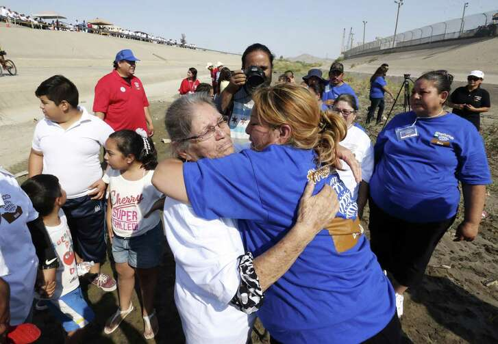"""photo, Erendira Fraire (right) rushes over to greet her mother, Esperanza Mata Lara whom she had not seen in 21 years during a brief meeting in the Rio Grande riverbed as part of the """"Hugs Not Walls"""" family reunification event on the U.S-Mexico border on June 24, 2017. Fraire traveled from Chicago while her mother traveled from Gomez Palacio, Durango, Mexico for the four-minute encounter."""