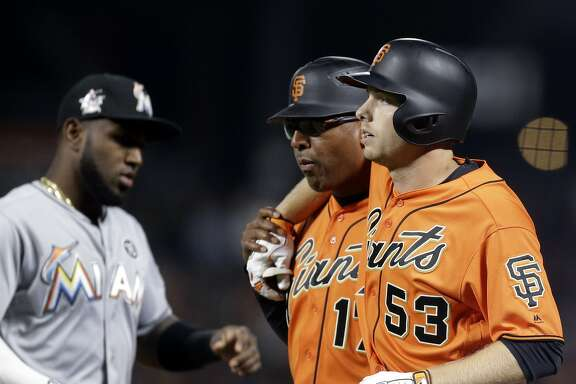 San Francisco Giants' Austin Slater, right, is assisted on the field by first base coach Jose Alguacil during the eighth inning of the team's baseball game against the Miami Marlins on Friday, July 7, 2017, in San Francisco. Slater left the game. (AP Photo/Ben Margot)