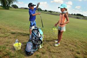 At right, Trinity Huckaby, 8, waits as her brother Bryce, 7, selects a driver before heading to the driving range at Babe Zaharias Golf Course in Port Arthur. (Mike Tobias/The Enterprise)