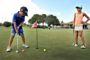 At right, Trinity Huckaby, 8, watches as her brother Bryce, 7, takes a turn on the practice putting green at Babe Zaharias Golf Course in Port Arthur. (Mike Tobias/The Enterprise)
