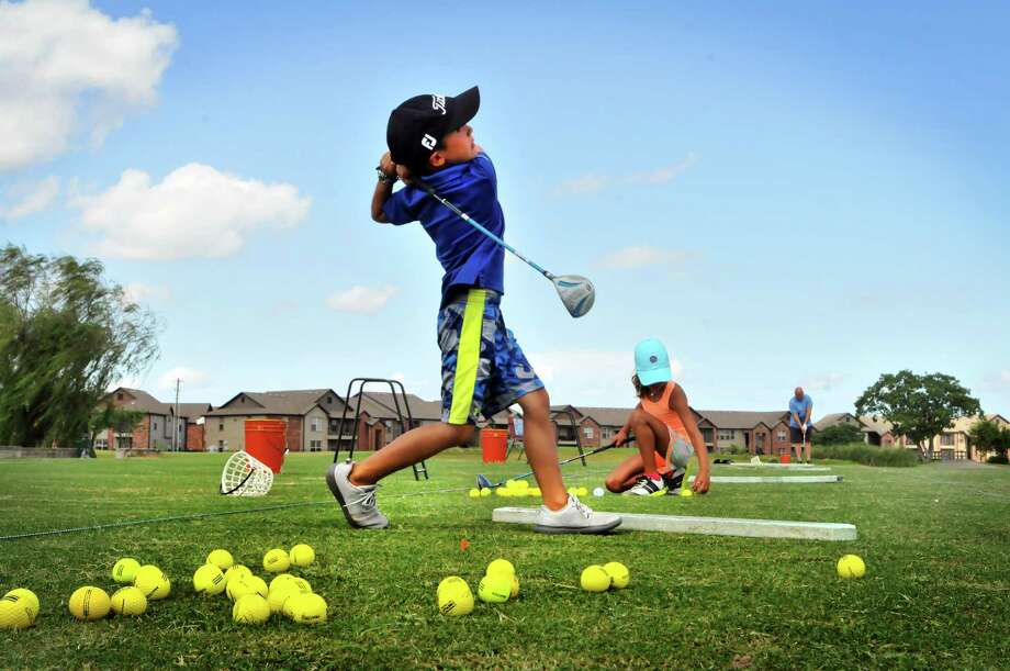 Bryce Huckaby, 7, takes a swing on the driving range while his sister Trinity, 8, places a ball on her tee at Babe Zaharias Golf Course in Port Arthur. (Mike Tobias/The Enterprise) Photo: Mike Tobias/The Enterprise