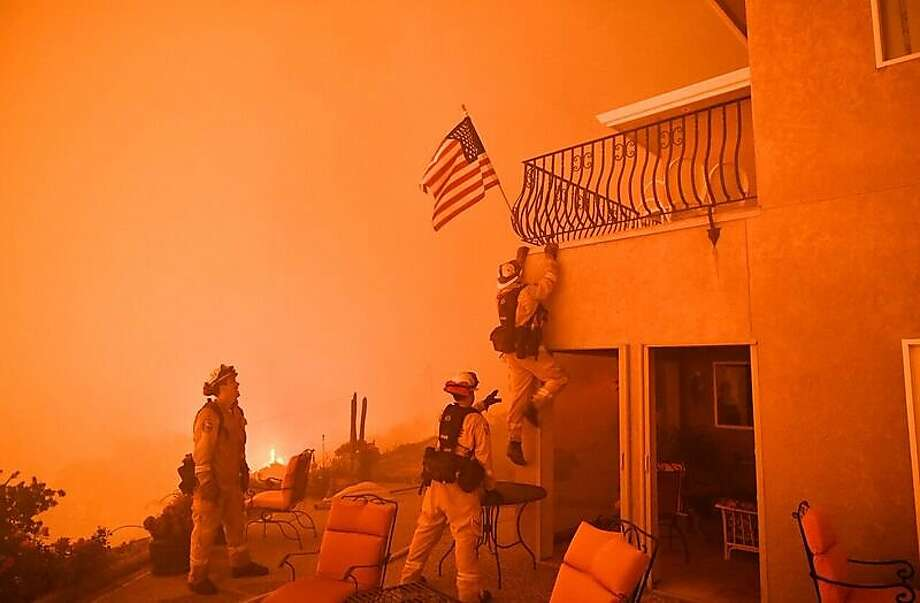 Firefighters save a US flag as impending flames from the Wall fire close in on a luxury home in Oroville, California on July 8, 2017. At least 10 structures have burned and the fire is currently at 20 percent containment. The first major wildfires after the end of California's five-year drought raged across the state on July 8, as it was gripped by a record-breaking heatwave.  Photo: JOSH EDELSON, AFP/Getty Images