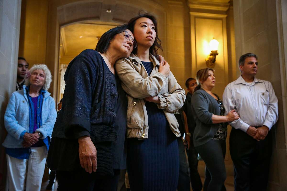 Jeanne Kwong (left) embraces Krista Gon (right) as they listen to a memorial service for the three victims of a shooting at a UPS facility last month at City Hall in San Francisco, California, on Sunday, July 9, 2017.