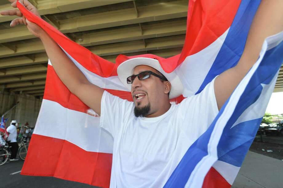 Juan Ortiz waves the flag over his shoulders while bikers pass during the 24th annual Puerto Rican Parade of Fairfield County on Sunday in Bridgeport. Thousands lined the parade route down Park Ave. while floats, dancers, clubs, politicians and civic organizations made their way to Seaside Park where the festivities continued. The theme of this year's parade was 'Power and Pride in Our Voices' Photo: Alex Von Kleydorff / Hearst Connecticut Media / Norwalk Hour