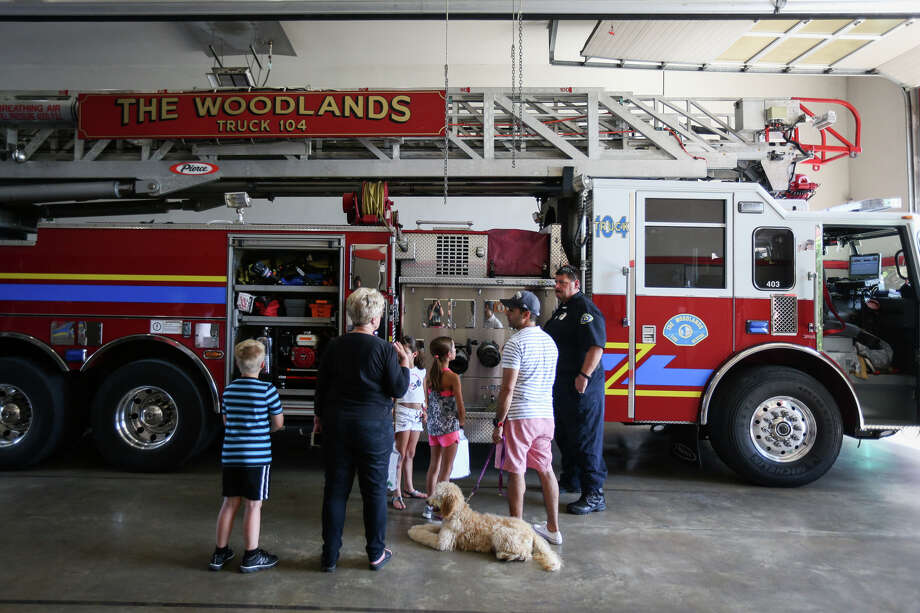 Firefighter Chris Mitcham answers questions and explains the ins and outs of a fire truck to attendees of the Public Safety Open House on Sunday at The Woodlands Fire Station 4. Photo: Michael Minasi, Staff Photographer / © 2017 Houston Chronicle